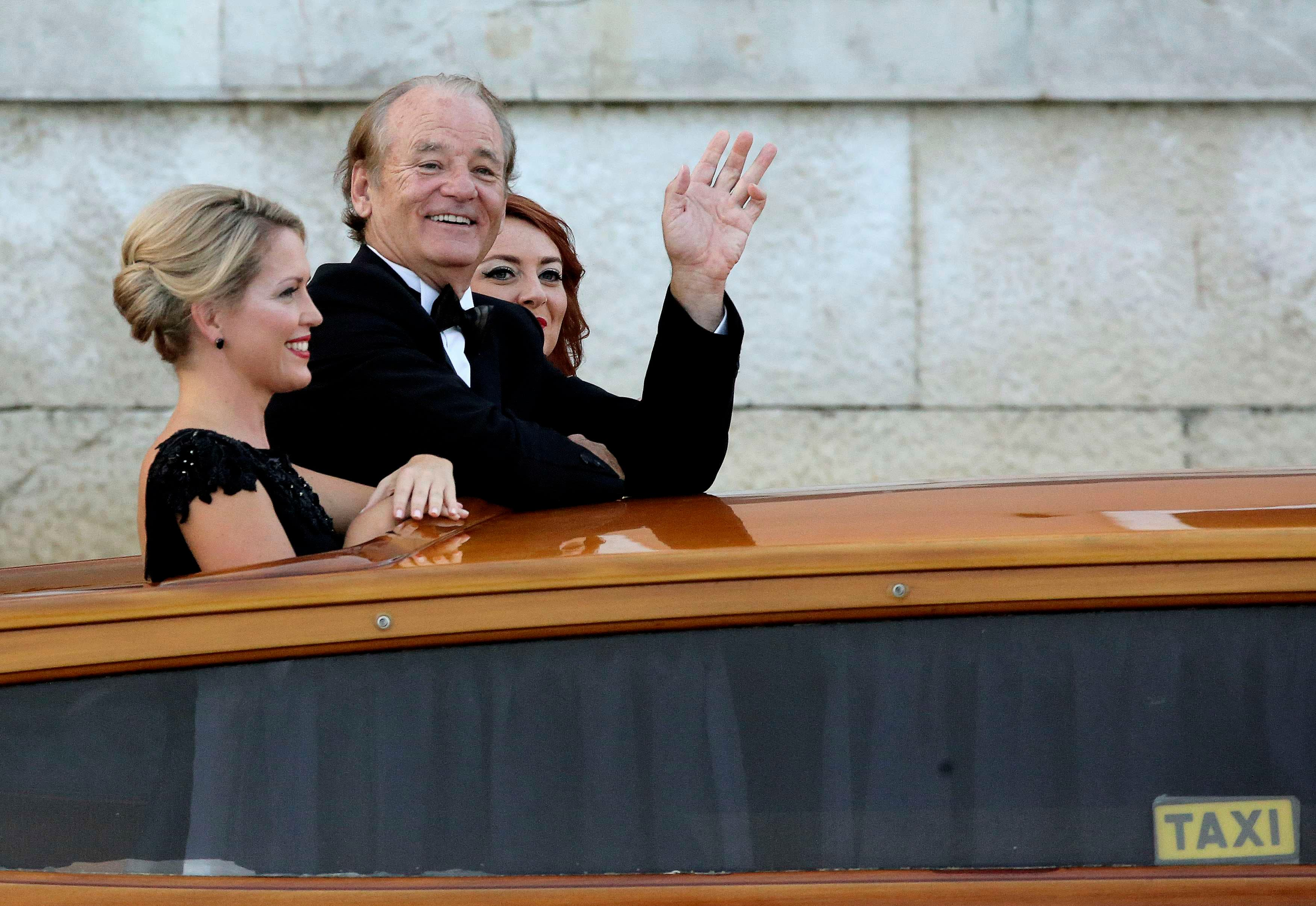 U.S. actor Bill Murray waves as he boards a taxi boat transporting guests to the venue of a gala dinner ahead of the official wedding ceremony, in Venice September 27, 2014.  (Reuters)