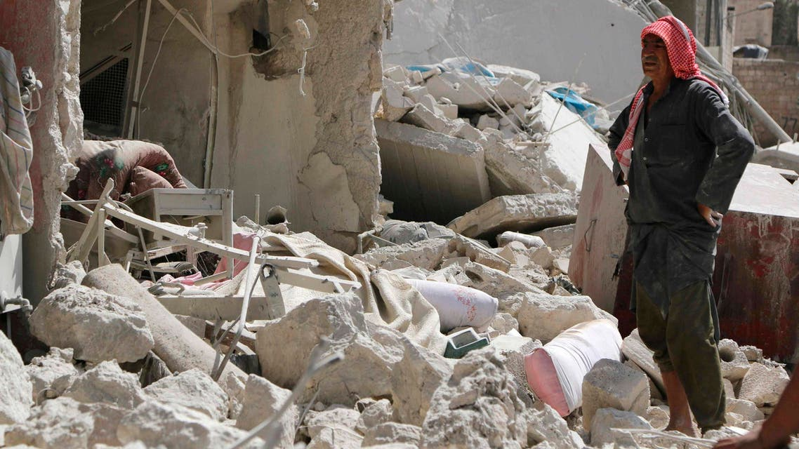 A man stands amidst debris as he inspects collapsed buildings at a site hit by what activists said were barrel bombs dropped by forces of Syria's President Bashar al-Assad, in Aleppo's al-Sakhour district, September 27, 2014.  (Reuters)