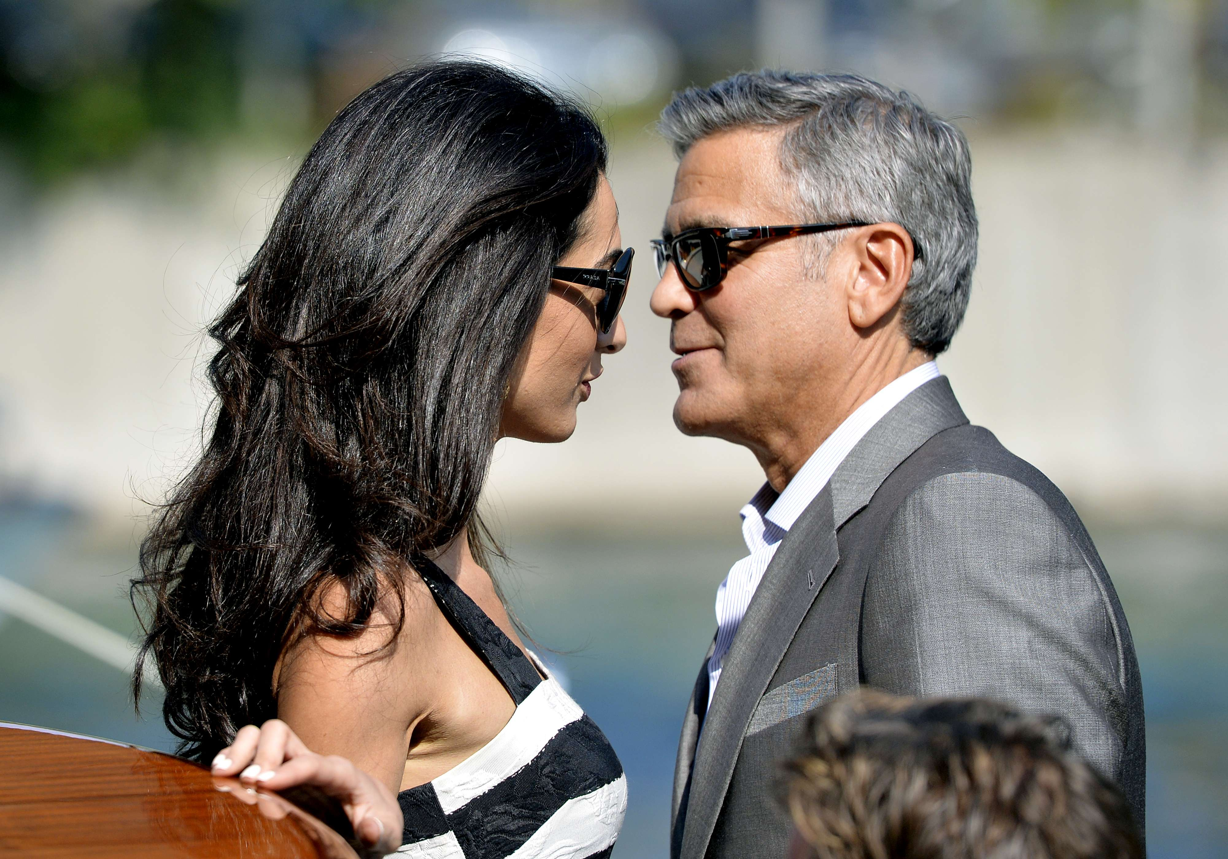 US actor George Clooney (R) and his Lebanon-born British fiancee Amal Alamuddin take a taxiboat upon their arrival in Venice on September 26, 2014. (AFP)