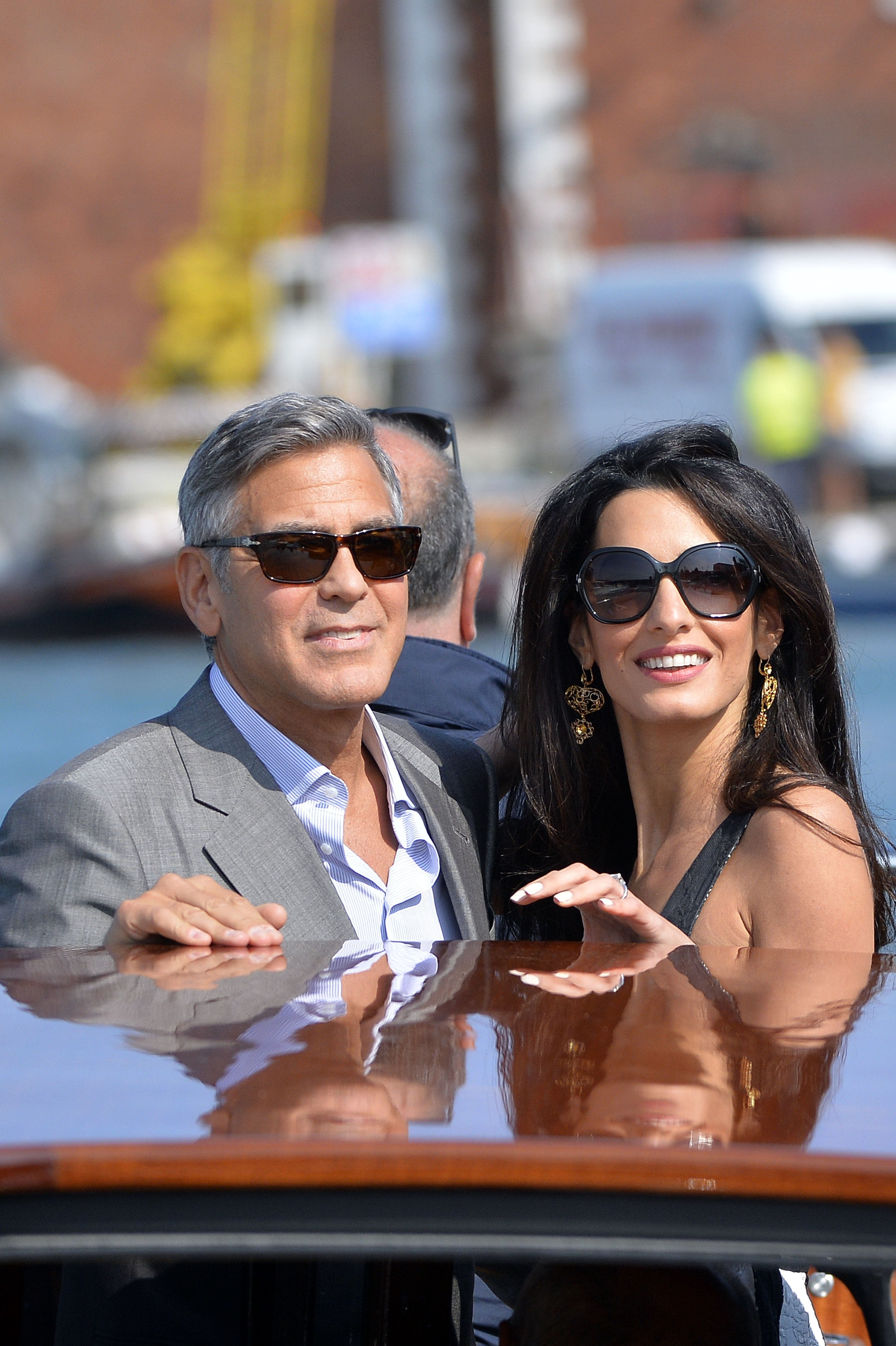 George Clooney (L) and Amal Alamuddin (R), his Lebanon-born British fiancee take a taxiboat upon their arrival in Venice, on September 26, 2014, on the eve of their wedding. (Reuters)