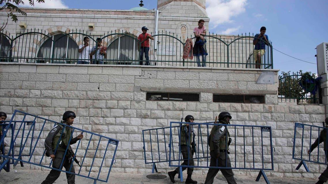 Israeli border policemen carry security barriers before Palestinian Muslim worshippers perform traditional Friday prayers in the Arab east Jerusalem neighbourhood of Ras al-Amud September 26, 2014.  (Reuters)