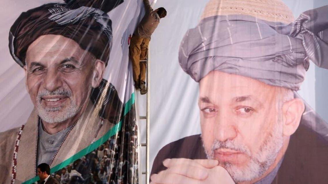 An Afghan boy prepares a banner of Afghan president-elect, Ashraf Ghani Ahmadzai (L), next to a banner of outgoing President Hamid Karzai. (Courtesy: AP)