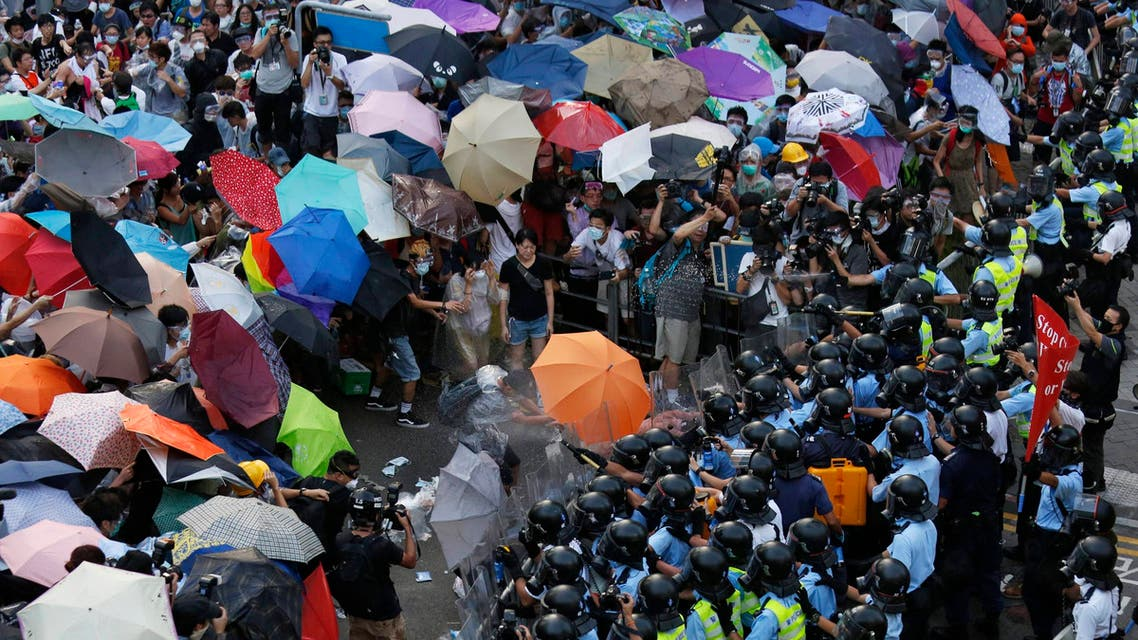 Protesters carrying umbrellas brave pepper spray used by riot police as tens of thousands of demonstrators block the main street to the financial Central district outside the government headquarters in Hong Kong September 28, 2014. (Reuters)