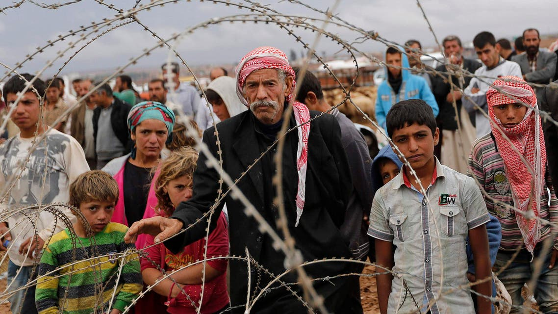 Syrian Kurds wait behind the border fences to cross into Turkey near the southeastern town of Suruc in Sanliurfa province September 28, 2014. (Reuters)