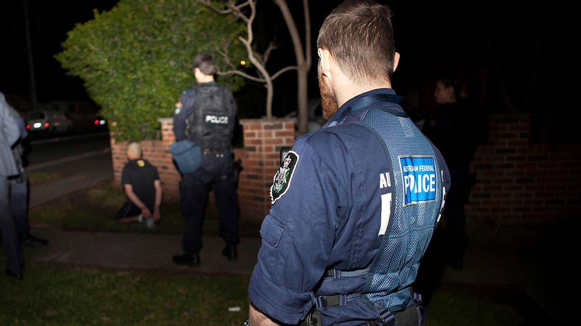 An Australian Federal Police officer and a New South Wales policeman stand near a suspect (L) who was detained during a raid on a house in western Sydney. (File photo: Reuters)