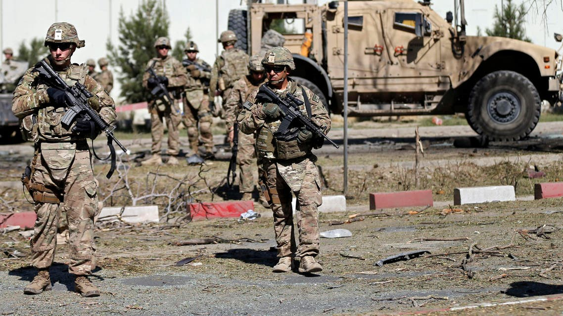 U.S. troops keep watch near a damaged vehicle at the site of a suicide attack in Kabul September 16, 2014. (Reuters)