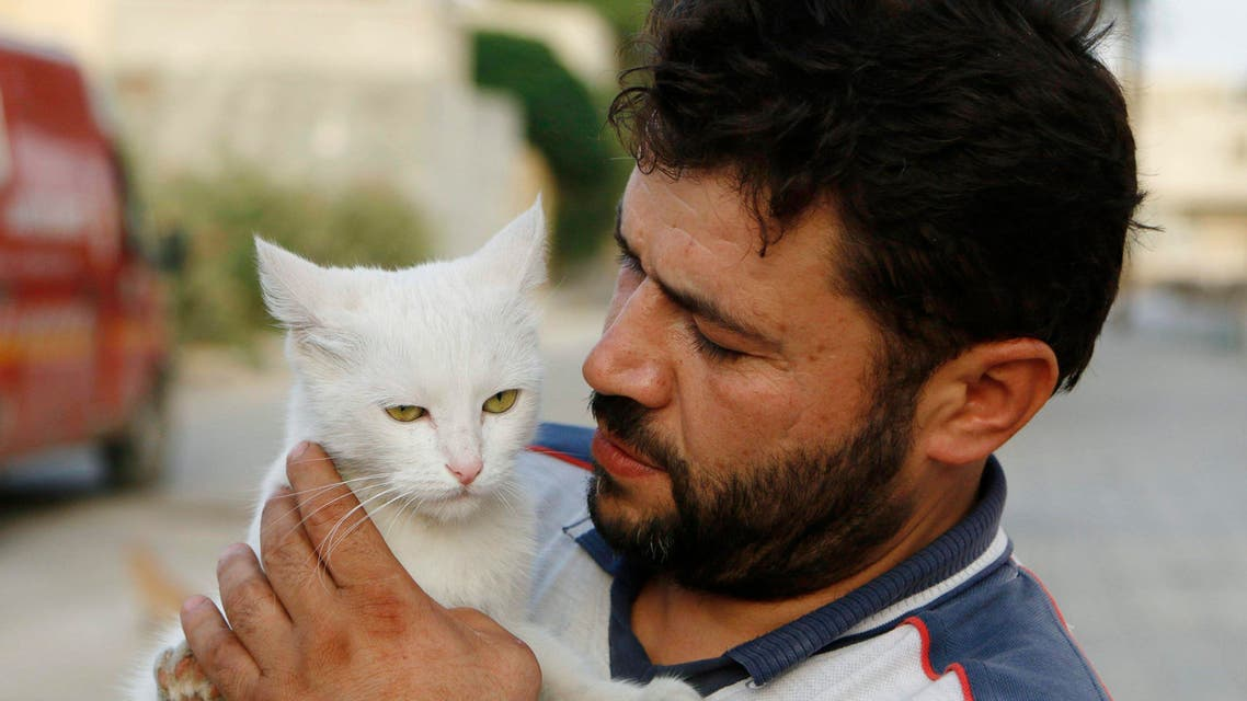 Alaa, an ambulance driver, carries a cat in Masaken Hanano in Aleppo, September 24, 2014. (Reuters)