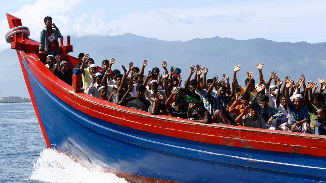 Ethnic Rohingya refugees from Myanmar wave as they are transported by a wooden boat to a temporary shelter in Krueng Raya in Aceh Besar in this April 8, 2013 file photo. (Reuters)