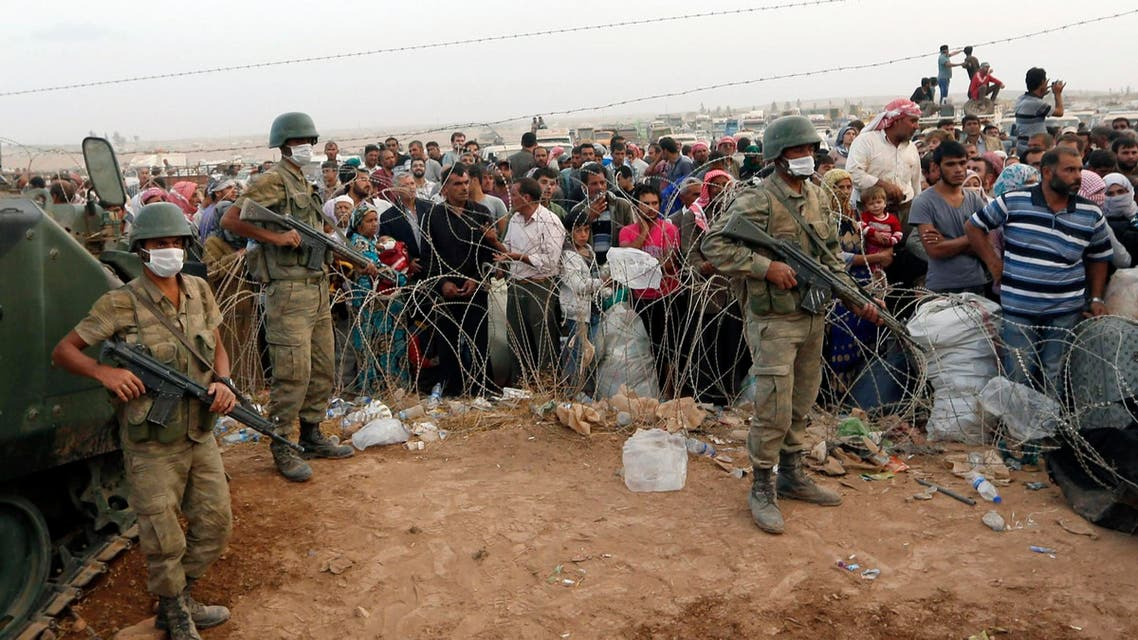 Turkish soldiers stand guard as Syrian Kurdish refugees wait behind the border fences to cross into Turkey near the southeastern town of Suruc in Sanliurfa province September 27, 2014.  (Reuters)