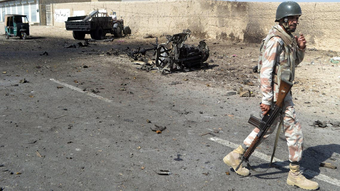 A Pakistani security personnel walks past a destroyed vehicle after a bomb blast in Quetta on October 4, 2014. (Reuters)