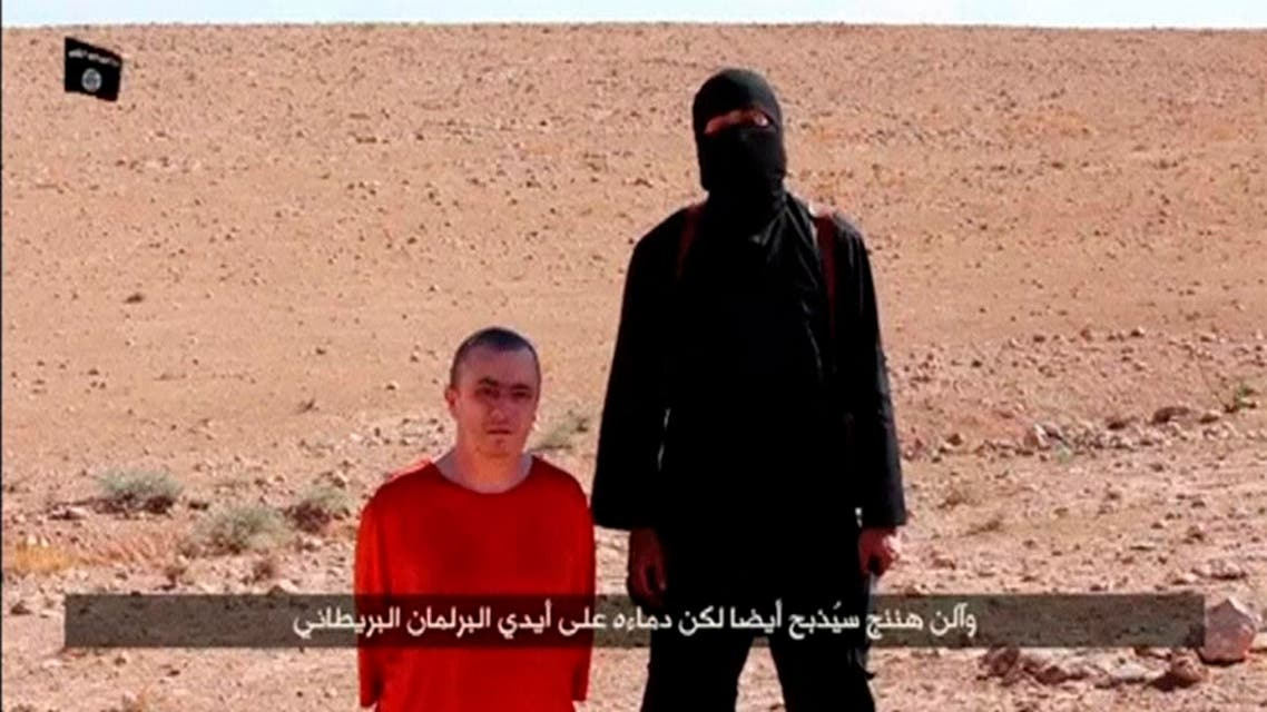 A masked man stands next to a kneeling man identified as British citizen Alan Henning (L), in this still image taken from video released by Islamic State militants fighting in Iraq and Syria, on October 3, 2014.