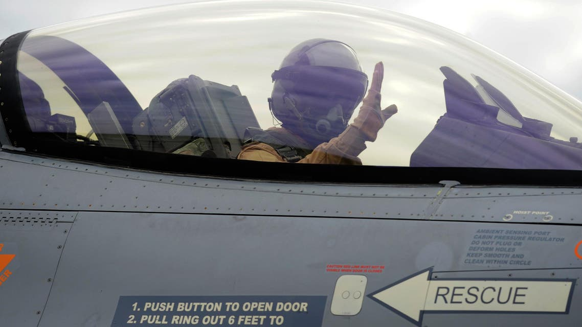 A Belgian F-16 fighter jet pilot gestures while taking off to join an international coalition fighting against ISIS