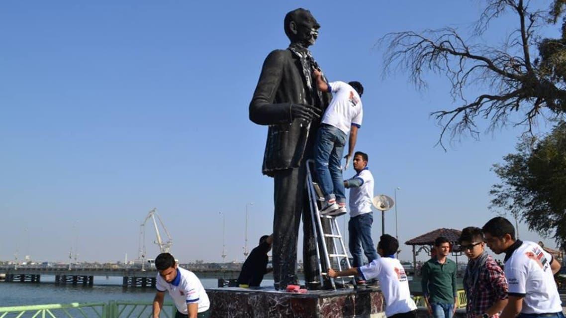 شباب يهيئون تمثال السياب للمناسبة
