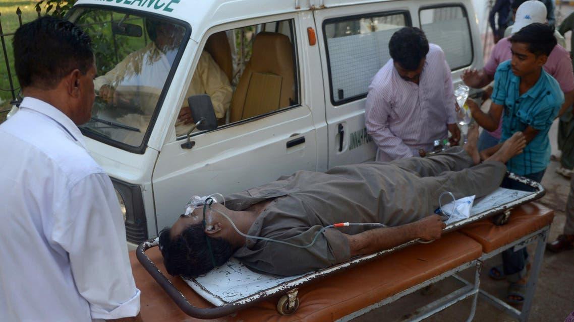Pakistani paramedics shift a liquor victim to a hospital in Karachi on Oct. 8, 2014. (AFP)