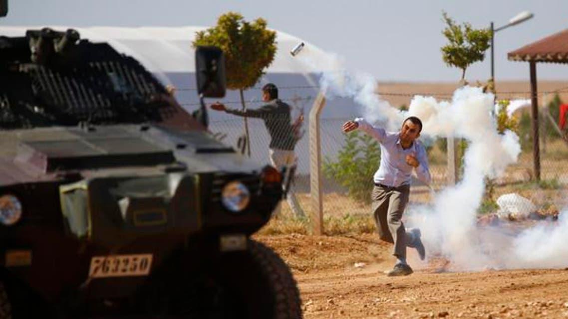 ایک کرد نژاد ترک باشندہ مظاہرہ کے دوران آنسو گیس کا شیل واپس سیکیورٹی فورسز کی جانب پھینک رہا ہے۔ [فائل فوٹو رائیٹرز]