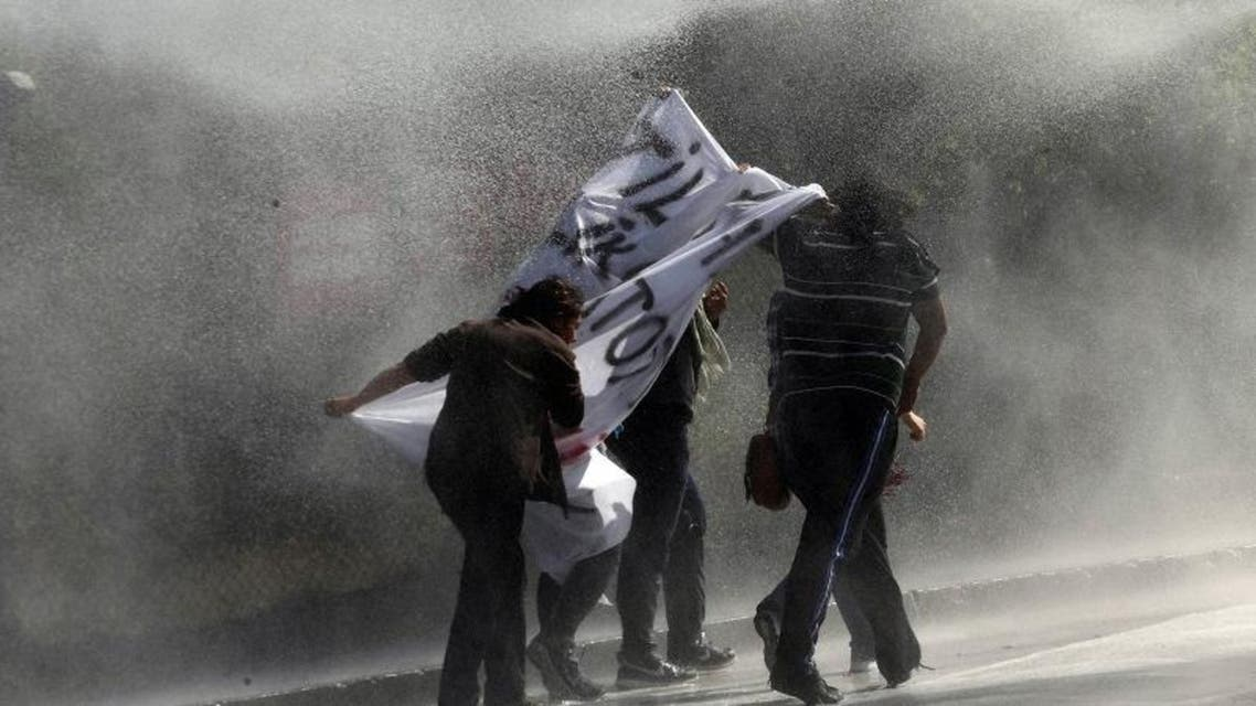 Demonstrators hold a banner as as they are sprayed by a water cannon during clashes with riot police outside of the Middle Eastern Technical University (METU) in Ankara on Oct. 9, 2014. (AFP)