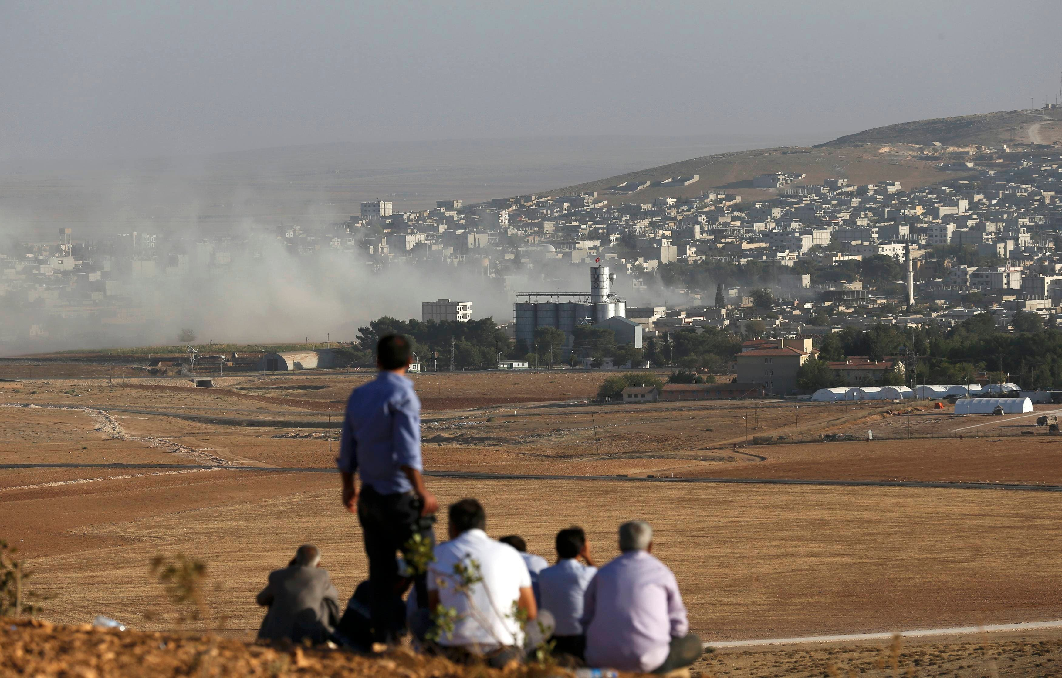 Turkish Kurds look towards the Syrian Kurdish town of Kobani from the top of a hill close to the border line between Turkey and Syria near Mursitpinar bordergate October 10, 2014. (Reuters) Kobane