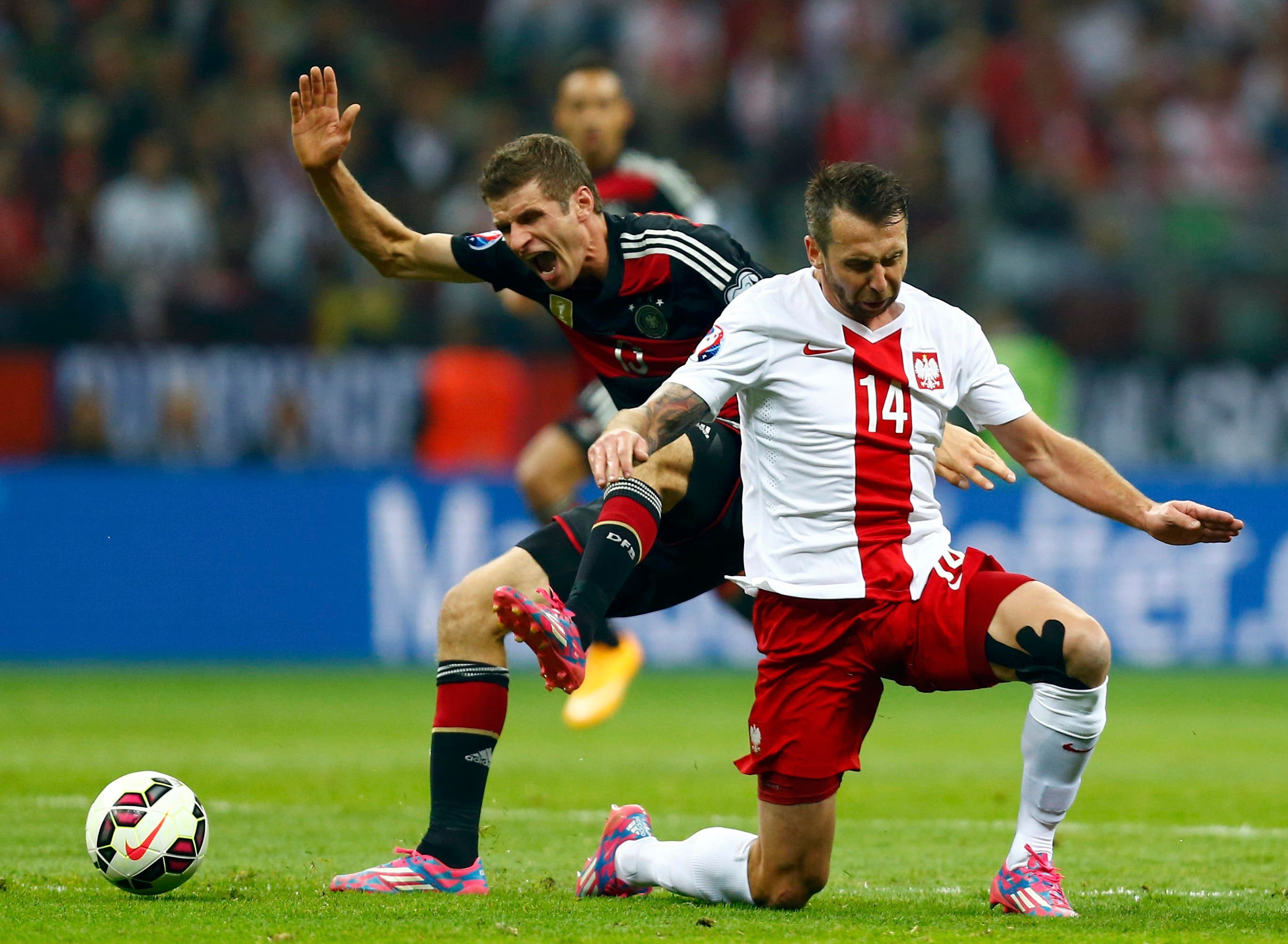 Germany's Thomas Mueller (L) challenges Poland's Jakub Wawrzyniak during their Euro 2016 group D qualifying soccer match at the National stadium in Warsaw October 11, 2014.  (Reuters)