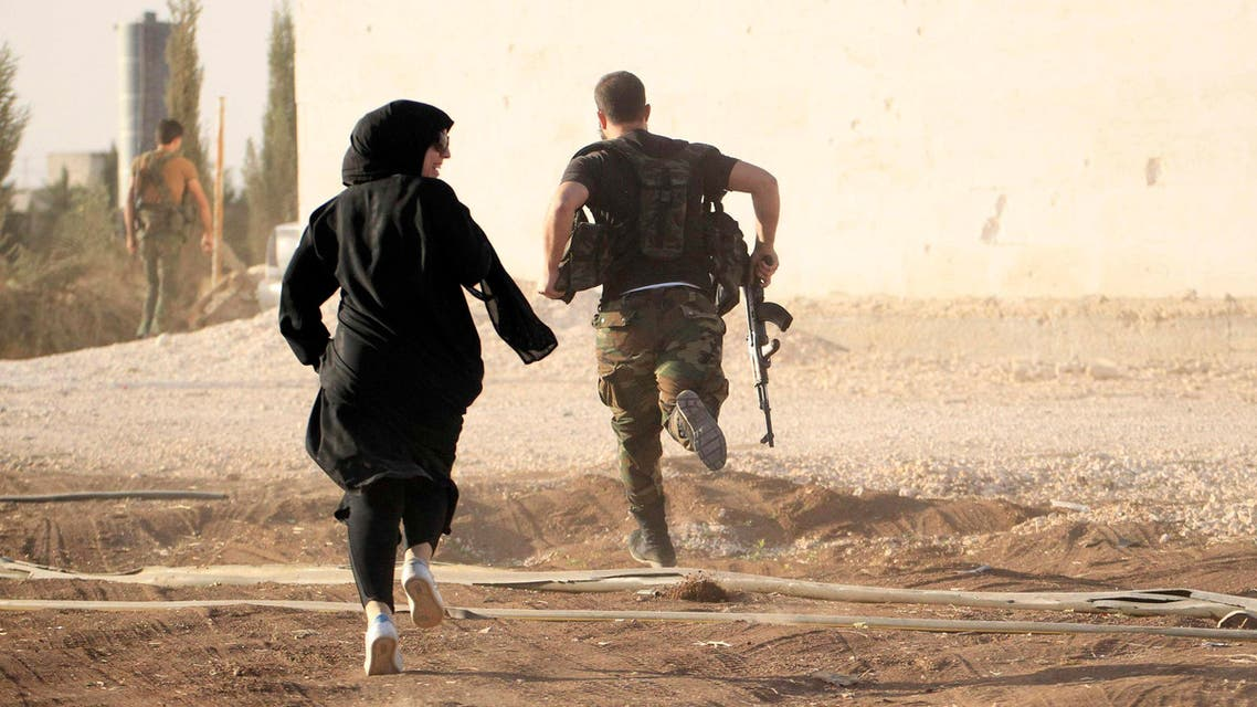 A woman reporter runs with a rebel fighter to avoid snipers at the frontline against the Islamic State fighters in Aleppo's northern countryside October 10, 2014. (Reuters)