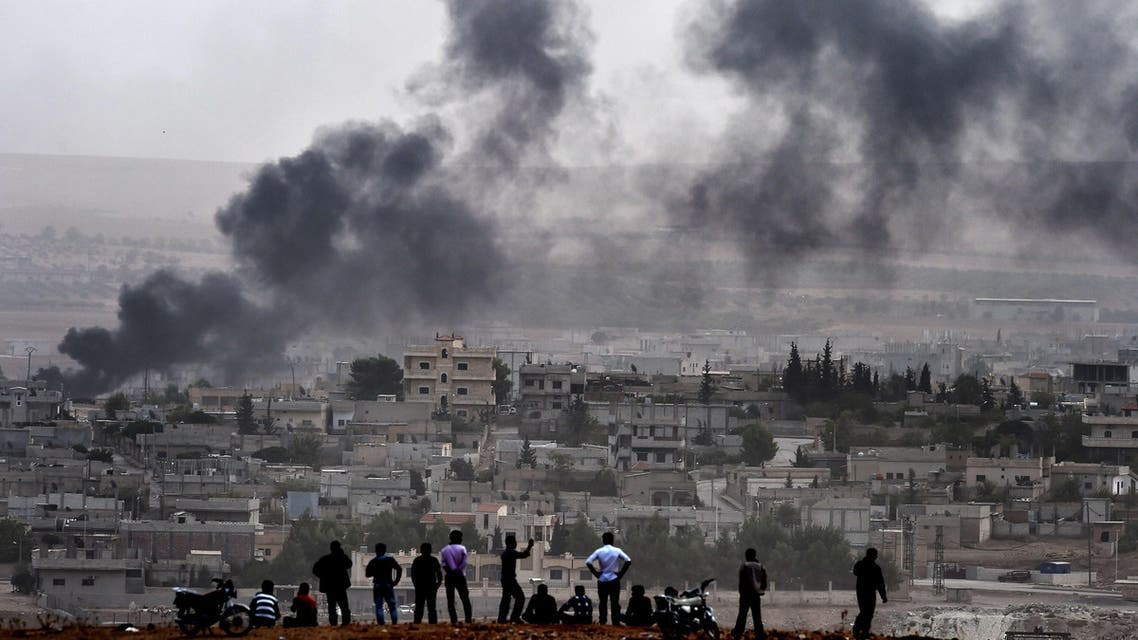 Kurdish people look at smoke rising from the Syrian town of Ain al-Arab, known as Kobane by the Kurds, from the Turkish-Syrian border, on October 11, 2014. (AFP)
