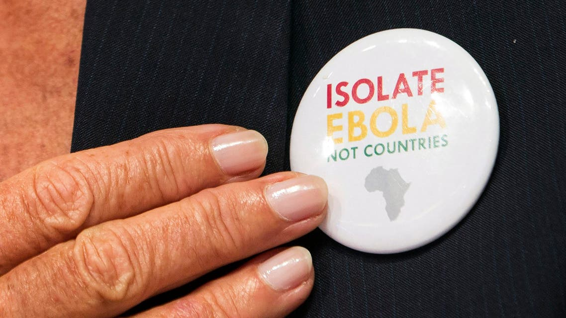 "International Monetary Fund (IMF) Managing Director Christine Lagarde points to a button saying ""Isolate Ebola, Not Countries"" as she speaks during the IMFC news conference during the World Bank/IMF Annual Meeting in Washington October 11, 2014. (Reuters)"