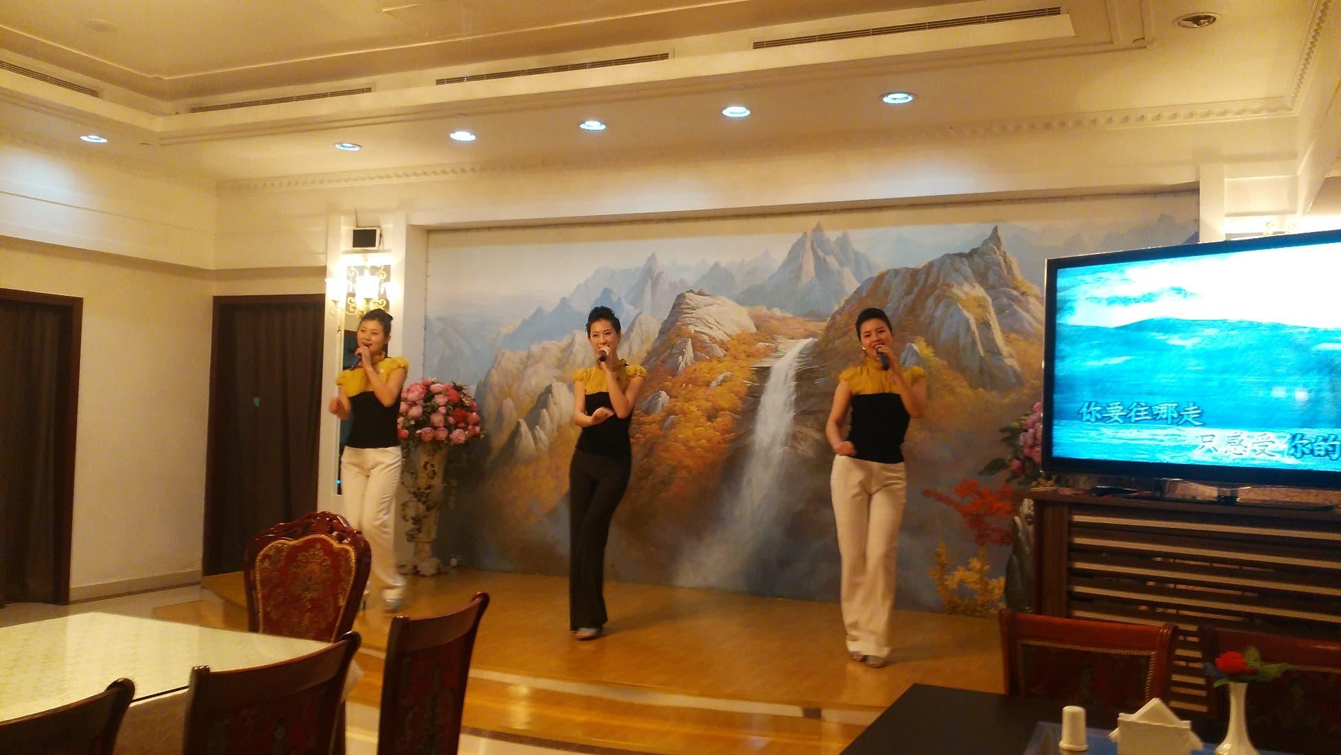 2- Dancers at the restaurant singing 'You are my superstar' with the aid of a karoke machine. All Okryu-gwan staff wear small North Korean flags pinned to their uniforms. (Al Arabiya)
