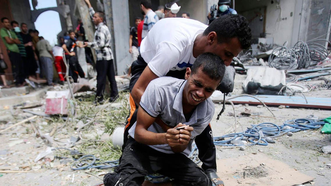A Palestinian reacts after his mother's body was removed from the rubble of their house which witnesses said was destroyed by an Israeli air strike, in Rafah, southern Gaza in this August 4, 2014 file photo.