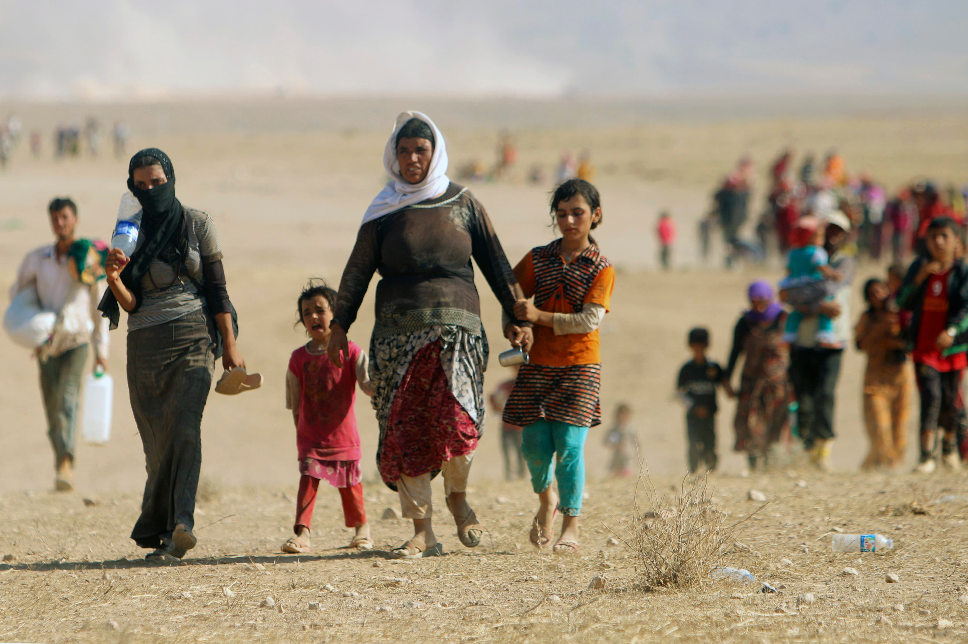 Displaced people from the minority Yazidi sect, fleeing violence from forces loyal to ISIS in Sinjar town, walk towards the Syrian border, on the outskirts of Sinjar mountain, near the Syrian border. (File photo: Reuters)