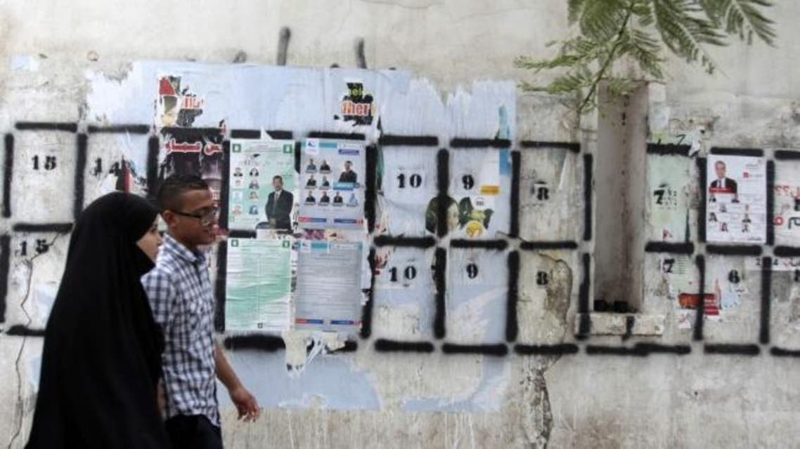 People walk past posters for parliamentary elections in Tunis(Reuters)