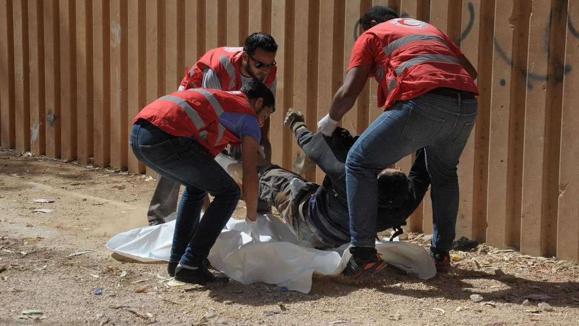Members of the Libyan Red Crescent remove the body of a man from the street during clashes between soldiers and Islamists who control Benghazion Oct. 15, 2014. (AFP)