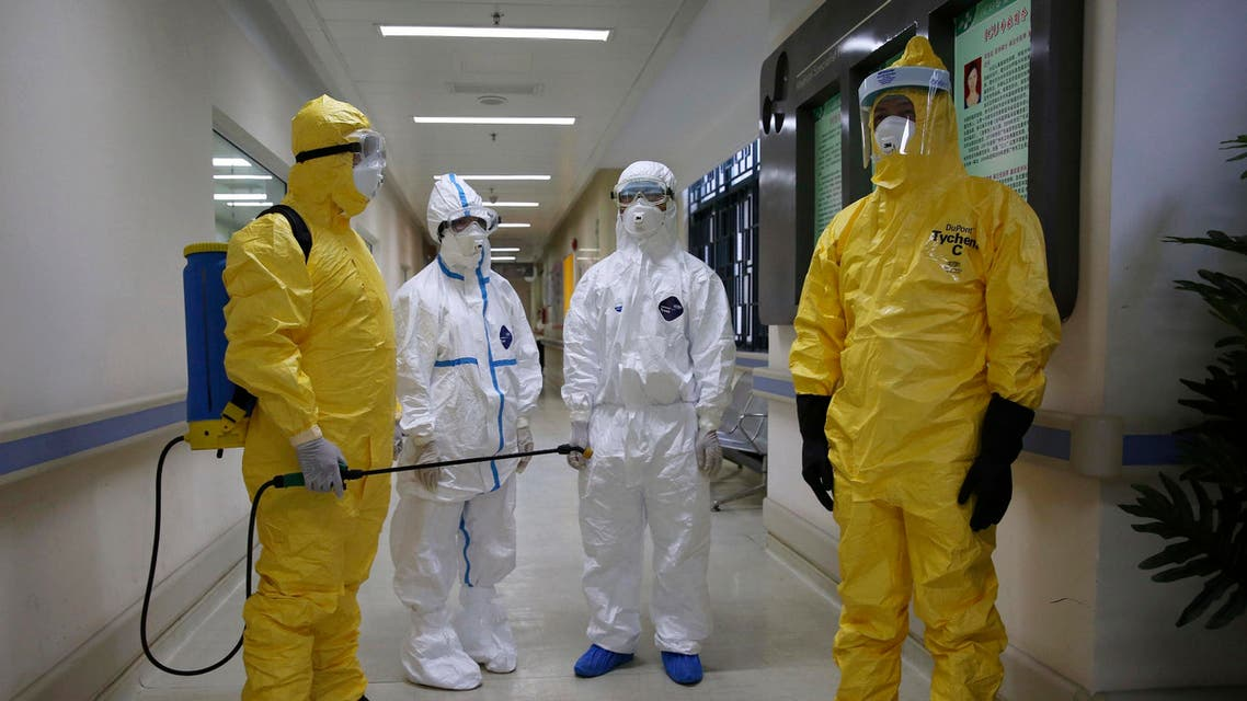 Health workers in protection suits wait in the corridor near a quarantine ward during a drill to demonstrate the procedures of handling Ebola victims, at a hospital in Guangzhou, Guangdong province October 16, 2014. (Reuters)