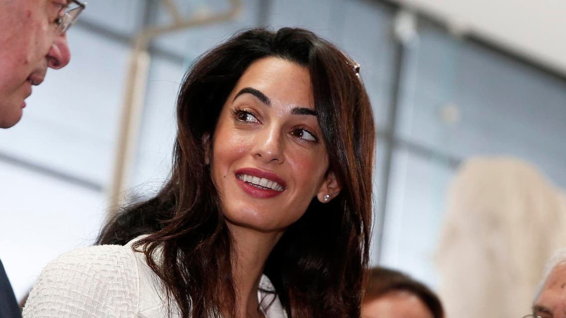 Human rights lawyer Amal Alamuddin Clooney (C) listens to Greece's Culture Minister Konstantinos Tasoulas during a visit at the Parthenon hall inside the museum in Athens October 15, 2014. (Reuters)