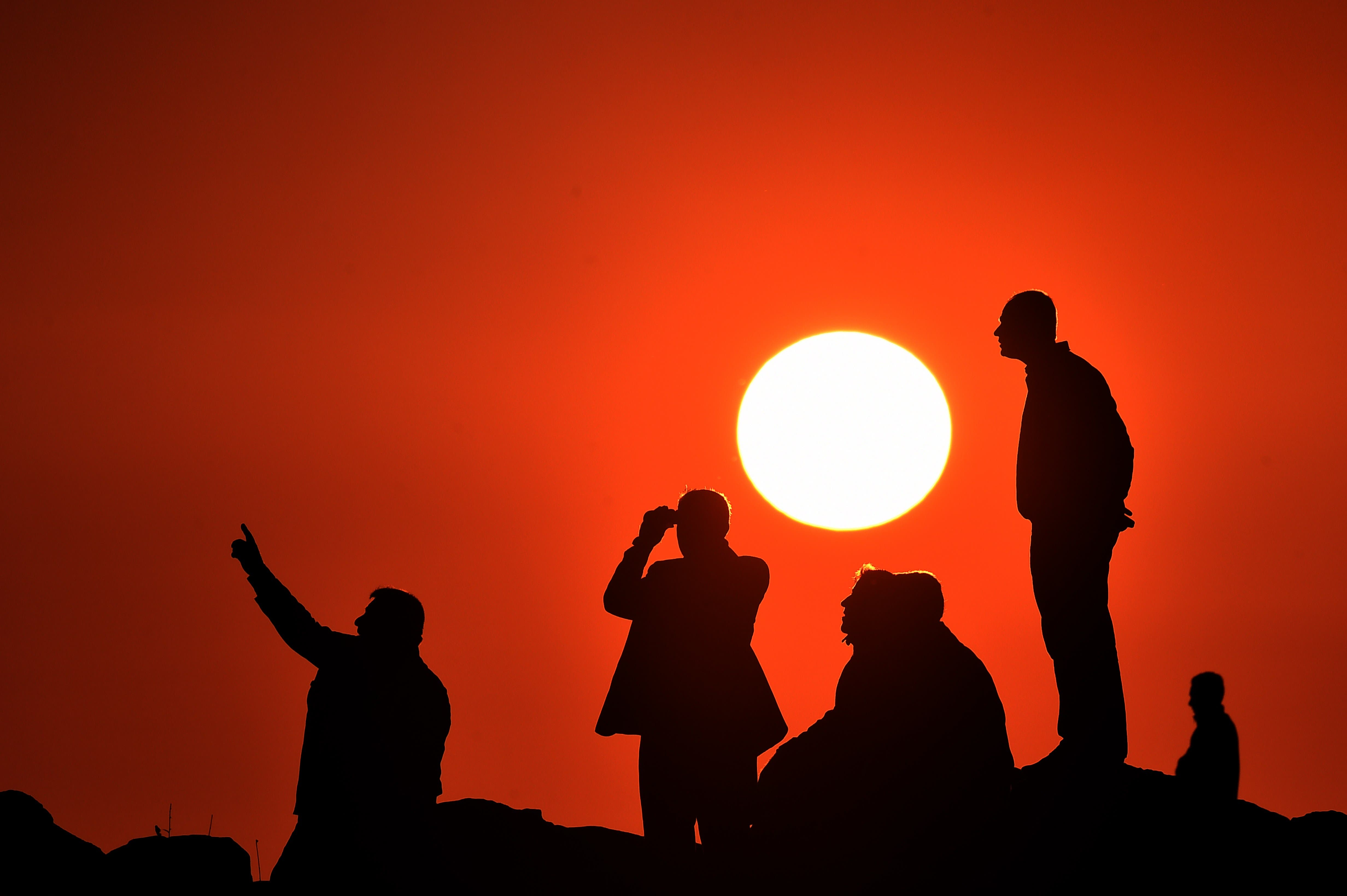Kurdish people watch the Syrian town of Kobane, also known as Ain al-Arab, from the Turkish border in the southeastern village of Mursitpinar, Sanliurfa province, on October 18, 2014.  (AFP)