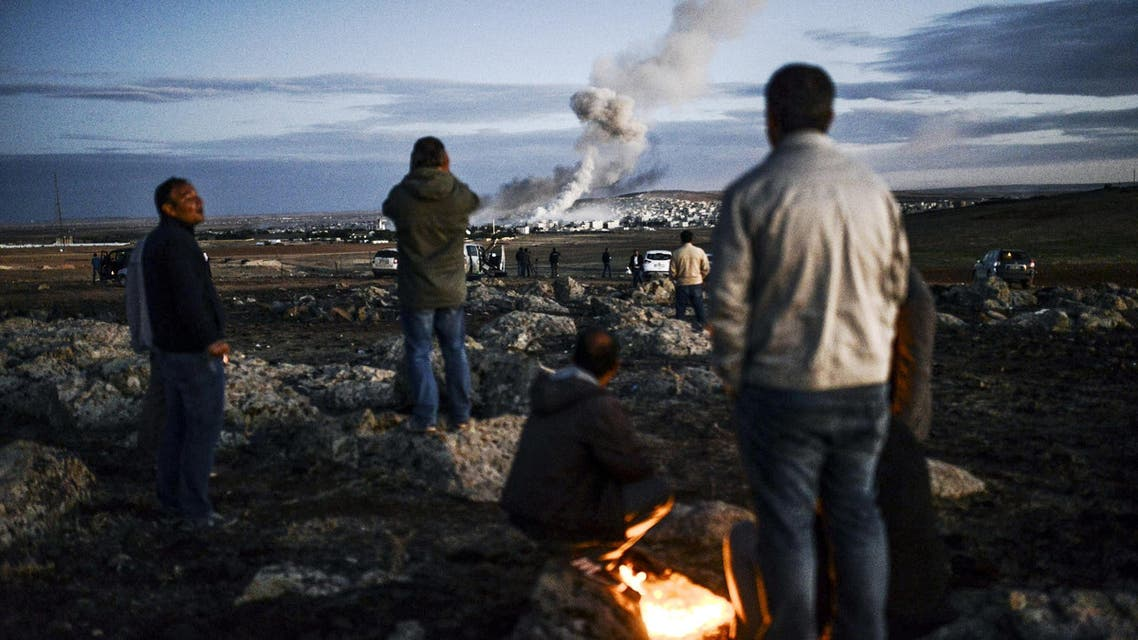 Kurdish people observe smoke rising from the Syrian town of Kobane, also known as Ain al-Arab, following an explosion as seen from the southeastern Turkish village on October 20, 2014. (AFP) 1