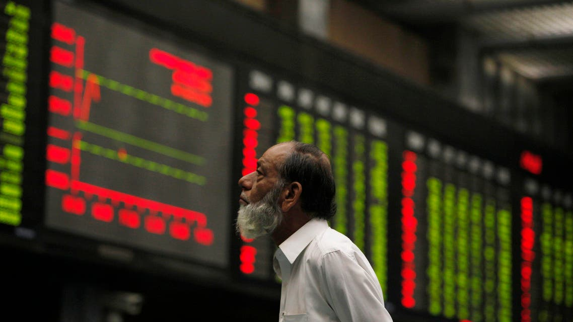 A broker monitors an electronic board displaying stock prices during a trading session at Karachi Stock Exchange October 16, 2014. (Reuters)