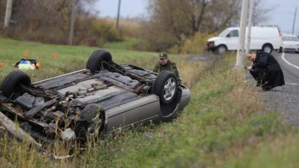 A Surete du Quebec (SQ) officer investigates an overturned vehicle in Saint-Jean-sur-Richelieu, Quebec October 20, 2014.