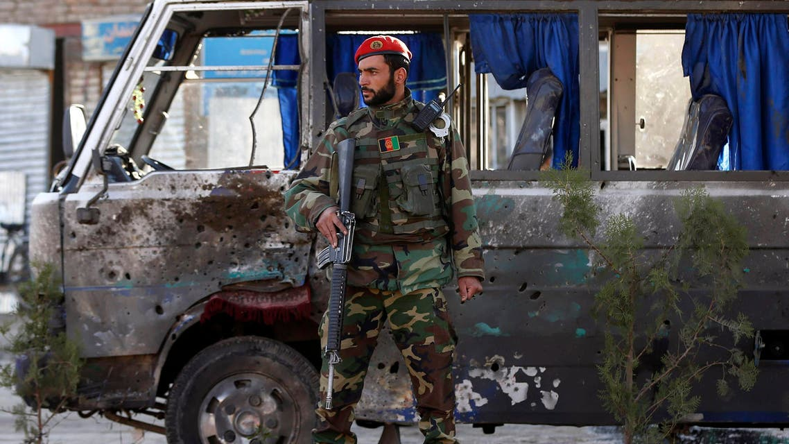 An Afghan national army soldier stands guard next to a bus which was hit by a remote-controlled bomb at the site of an incident in Kabul October 21, 2014. (Reuters)