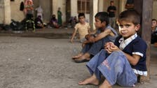 Many Iraq schools open a month late amid crowding by displaced