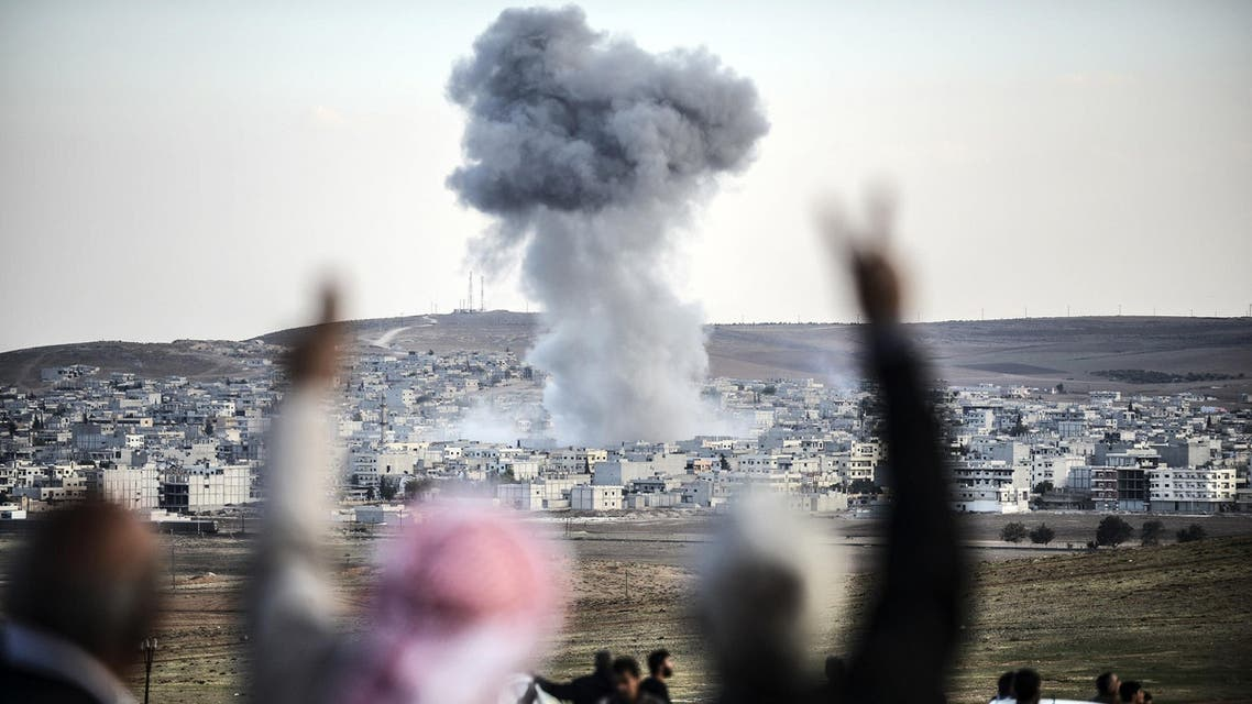 A picture taken from the southeastern Turkish village of Mursitpinar in the province of Sanliurfa shows people gesturing as smoke rises in the sky following an attack by jet aircrafts in the Syrian town of Kobane, also known as Ain al-Arab, on October 22, 2014. AFP
