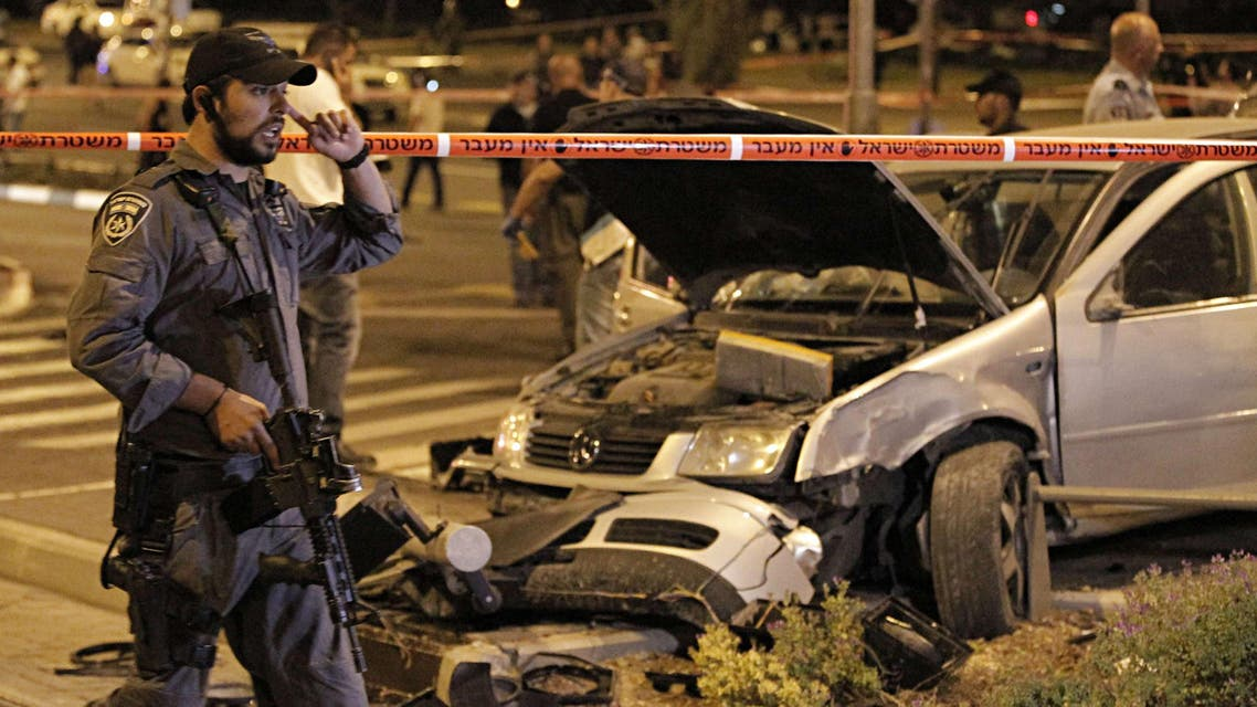Israeli policemen stand guard at the scene after a car rammed a group of pedestrians at the Ammunition Hill tram stop, which lies on the seamline between west and occupied east Jerusalem, injuring nine on Oct. 22, 2014. (AFP)