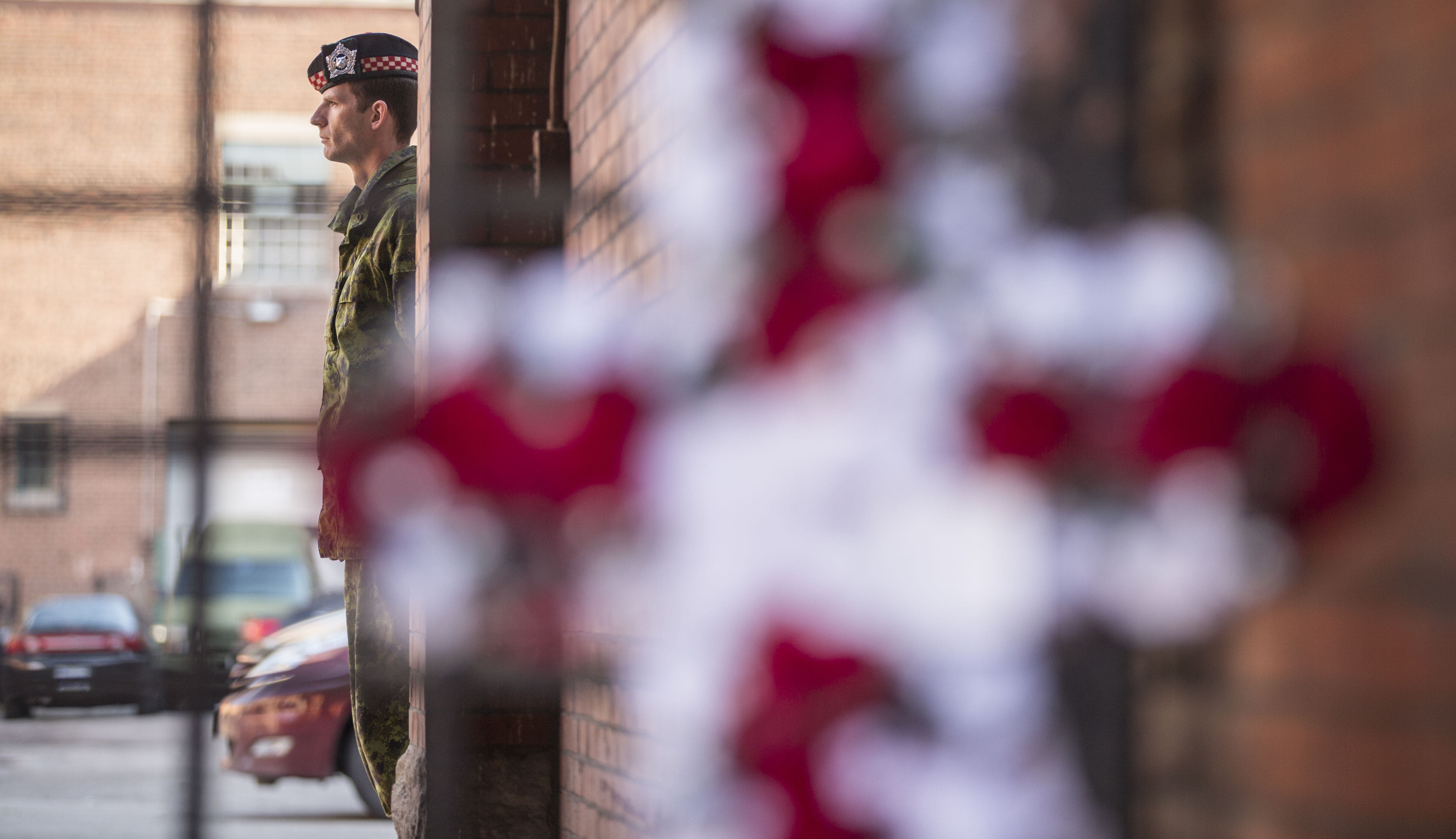 A floral memorial is seen as a soldier stands guard at the John Weir Foote V.C. Armouries in Hamilton, Ontario, October 22, 2014 after a soldier believed to be from the base was killed in an attack in Ottawa.
