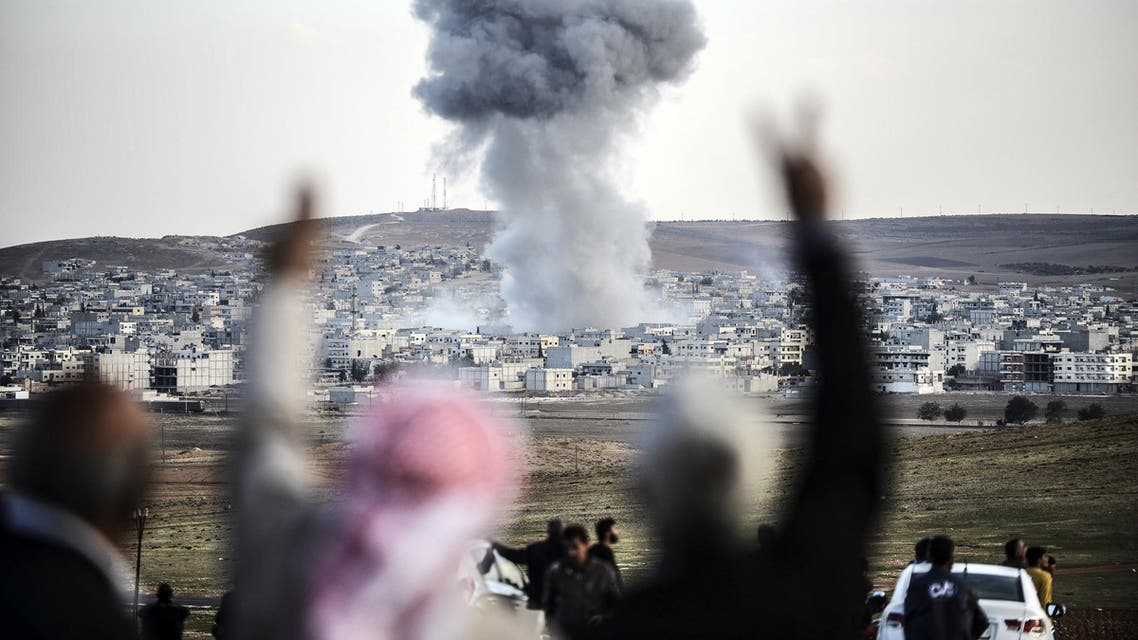 eople gesturing as smoke rises in the sky following an attack by jet aircrafts in the Syrian town of Kobane, also known as Ain al-Arab, on Oct. 22, 2014.  (AFP)