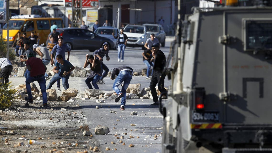 Palestinian youths from the Jalazoun refugee camp clash with Israeli security forces on a road at the entrance of the Jewish West Bank settlement of Beit El, north of Ramallah. (AFP)