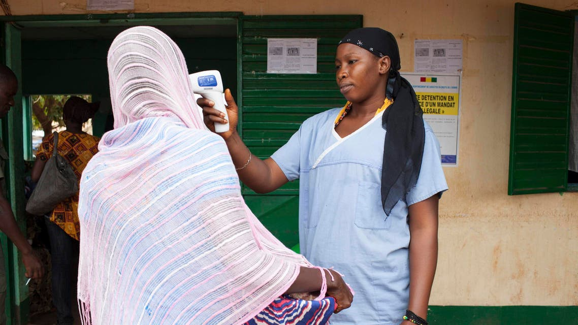A health worker checks the temperature of a woman leaving Guinea at the border with Mali in Kouremale, Oct. 2, 2014.  (AFP)