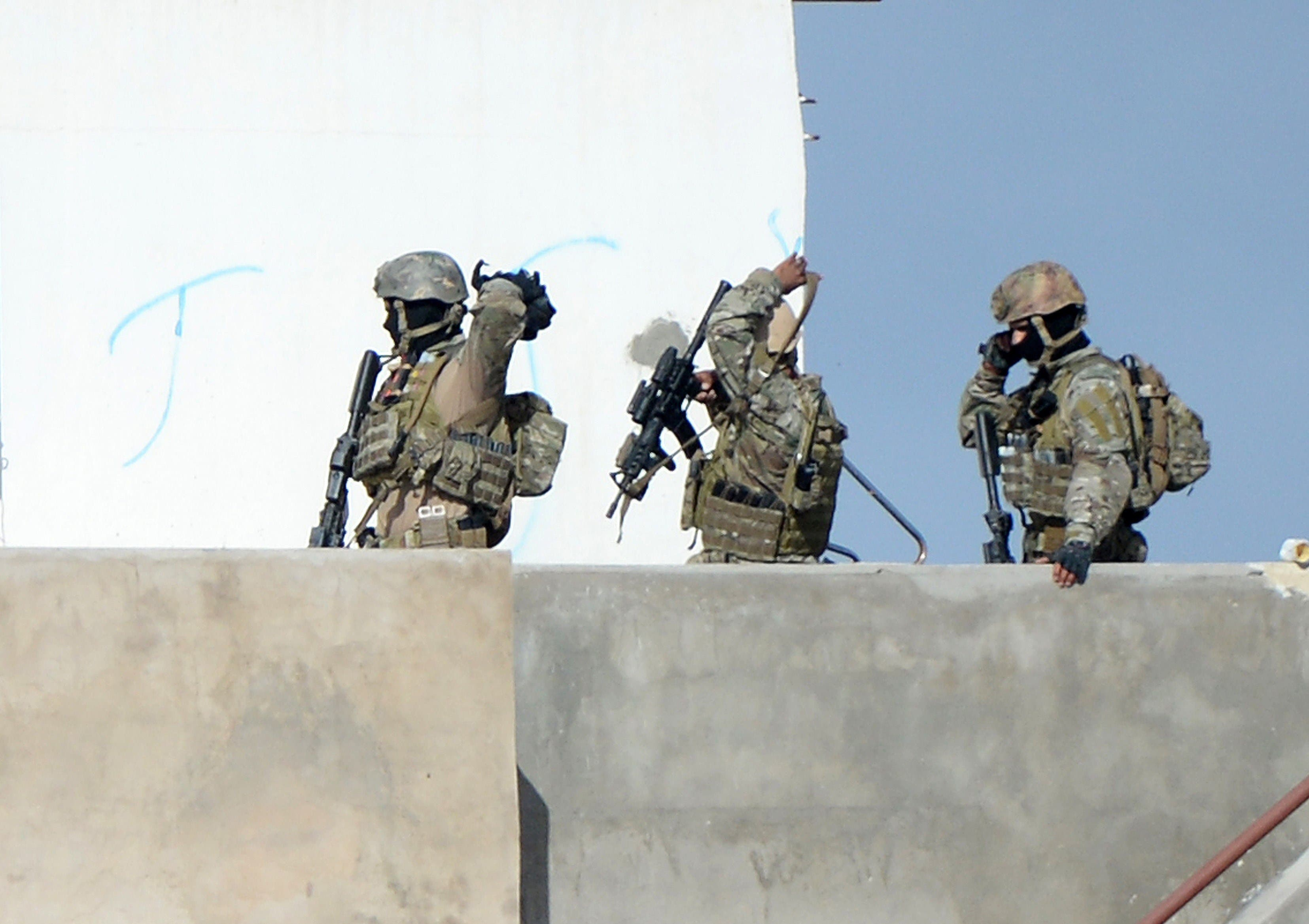 embers of the Tunisian military walk on a balcony during an operation against gunmen in the town of Oued Ellil near the Tunisian capital Tunis on Oct. 24, 2014. (AFP)