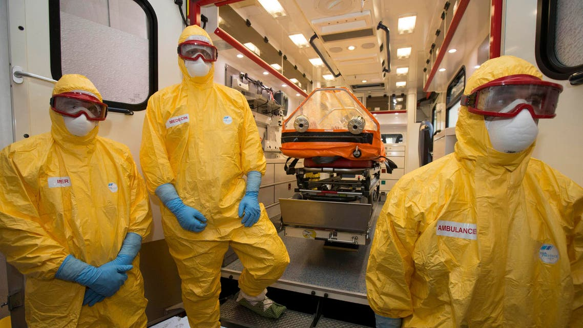 Staff of the emergency medical services in France (SAMU) dressed in Ebola virus protections outfits stand near a stretcher placed inside an ambulance at the Necker Hospital in Paris, October 24, 2014.  (Reuters)