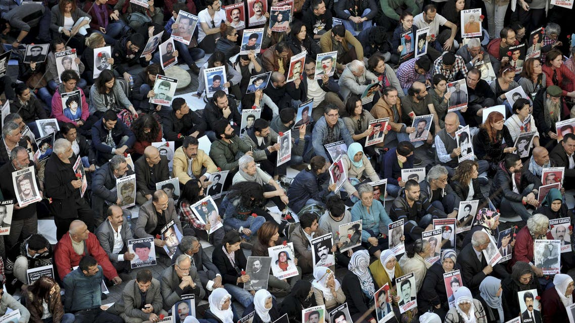 People hold pictures of disappeared people on October 25, 2014 as they gather on Istiklal avenue in Istanbul. AFP