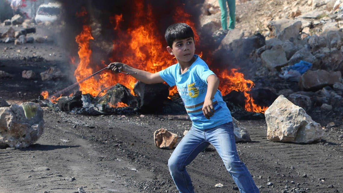 A Palestinian boy uses a sling to throw stones towards Israeli soldiers during clashes following a protest against the near-by Jewish settlement of Qadomem, in the West Bank village of Kofr Qadom near Nablus October 24, 2014. (File photo:Reuters)