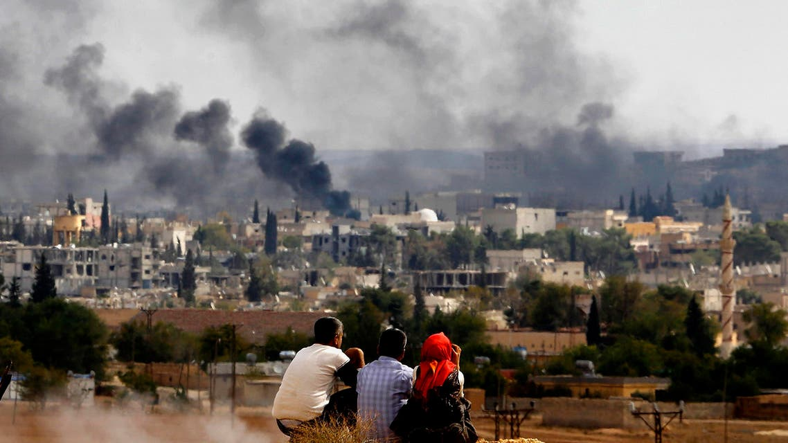 Kurdish refugees from Kobani watch as thick smoke covers the Syrian town of Kobane, October 26, 2014. (Reuters)