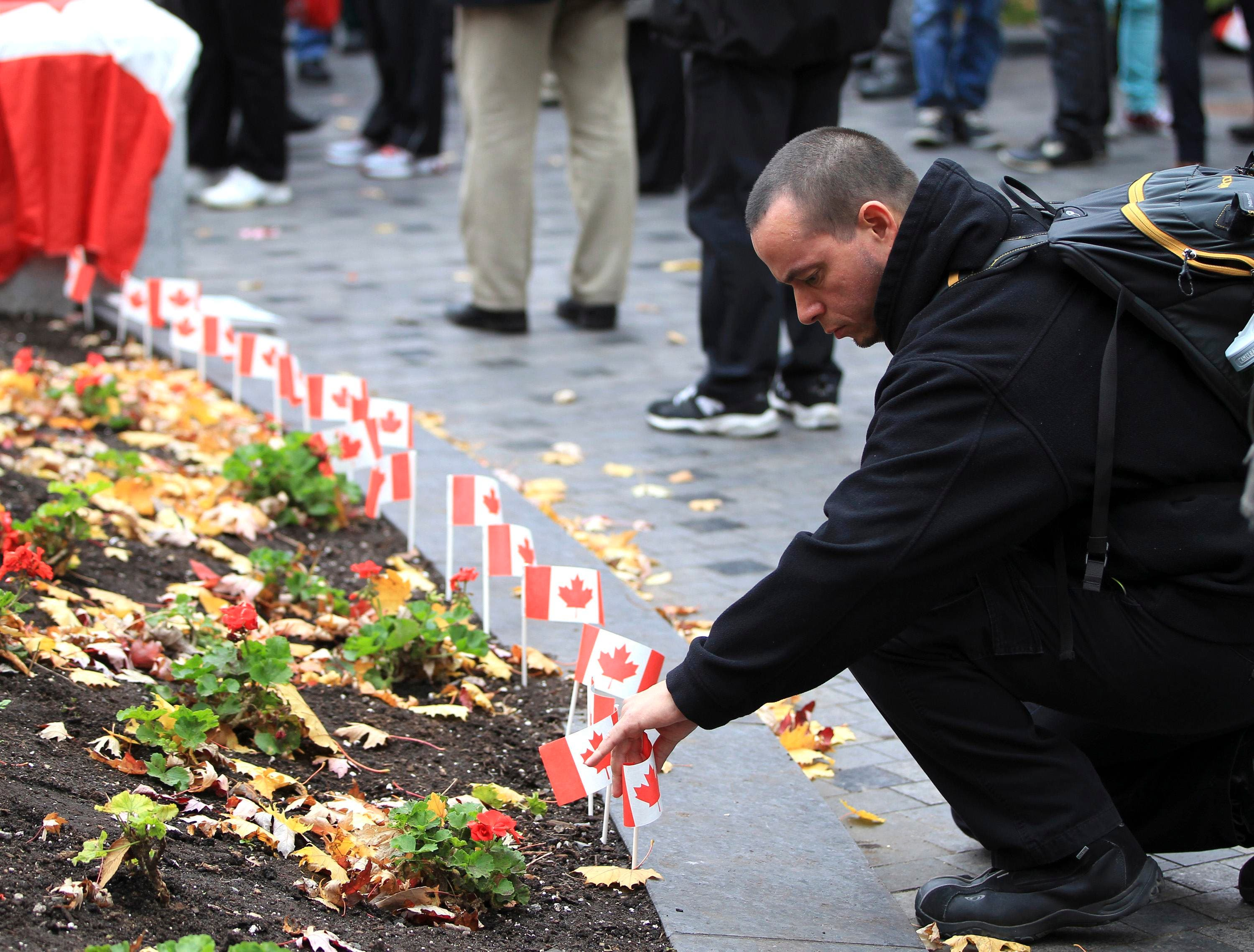 A man places a flag in memory of fallen Canadian soldiers, Warrant Officer Patrice Vincent and Corporal Nathan Cirillo, during a vigil in Montreal, October 25, 2014.